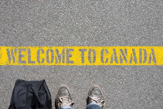 Shoes and bag on side of Welcome to Canada sign on asphalt
