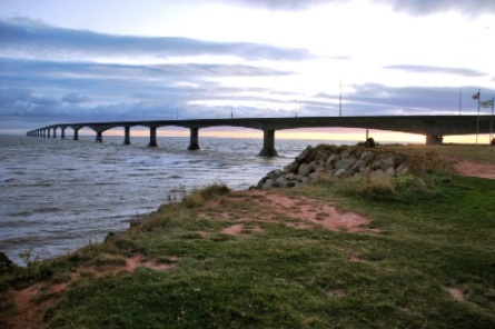 Confederation Bridge to Prince Edward Island with a beautifully lit sky and moving water under the bridge