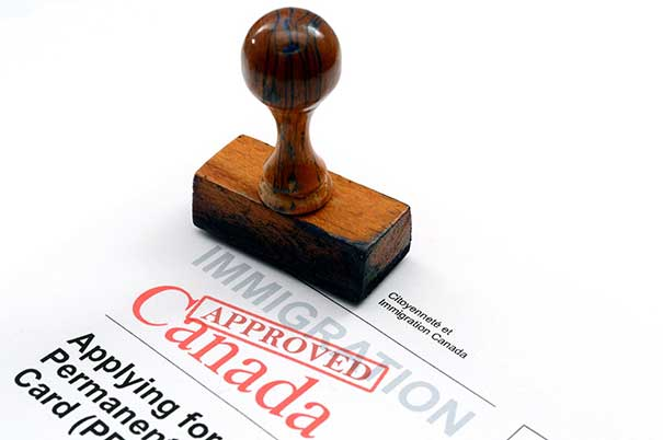 An application for migration to Canada was approved with the red stamp.