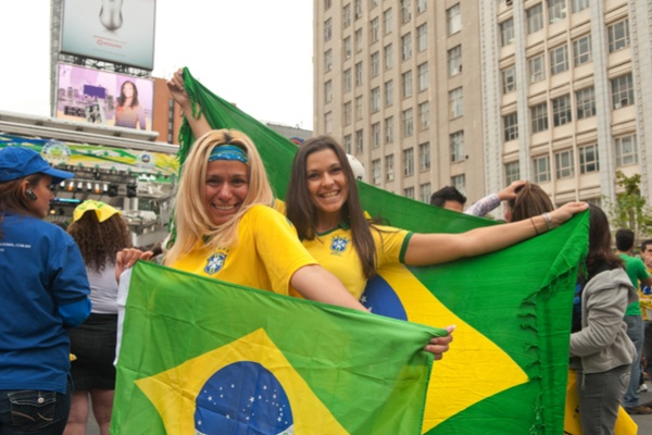 Two Brazilian ladies are proudly raising their National Flag.