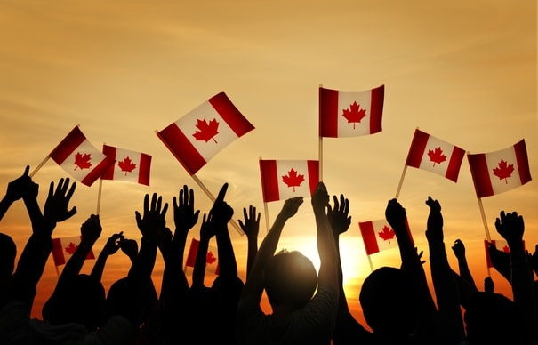 Dozens of people waving Canadian flags against the sunset
