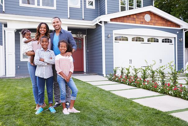A happy family is taking a picture while standing outside their newly bought house.