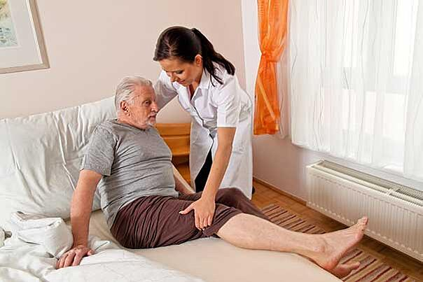 The old man is having a hard time getting out of his bed and the nurse was assisting him.