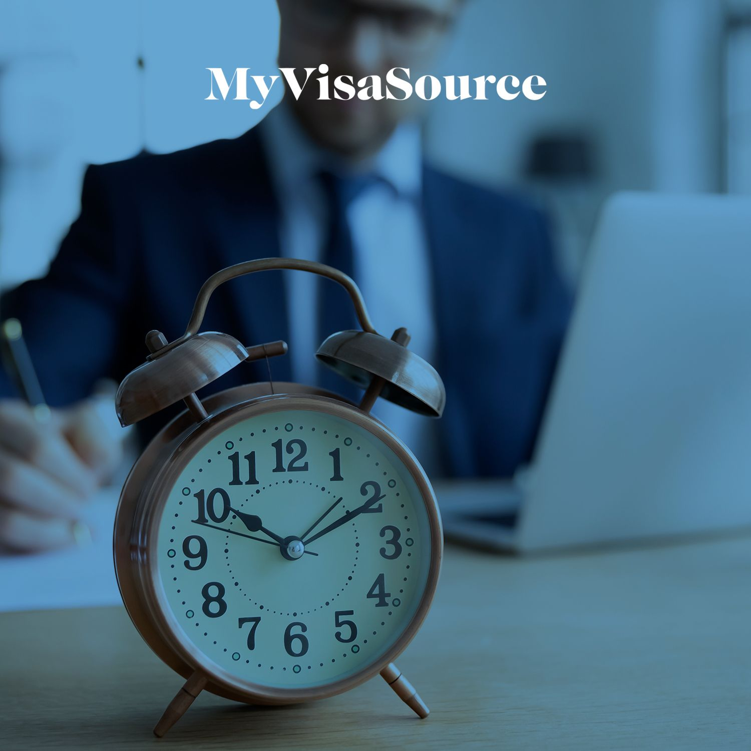clock in front of a man working at his desk my visa source