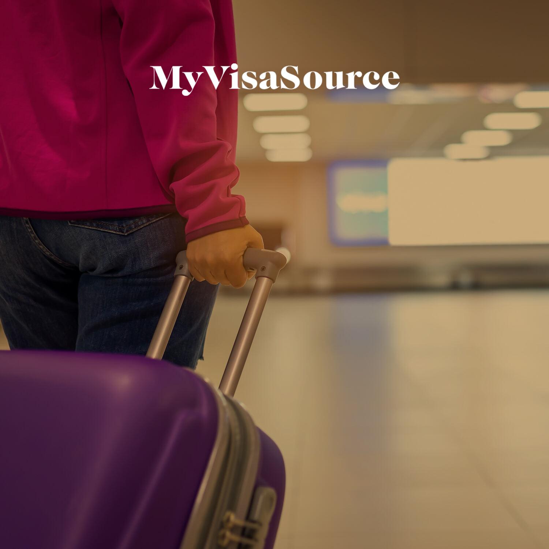 traveler with carryon walking through an airport my visa source