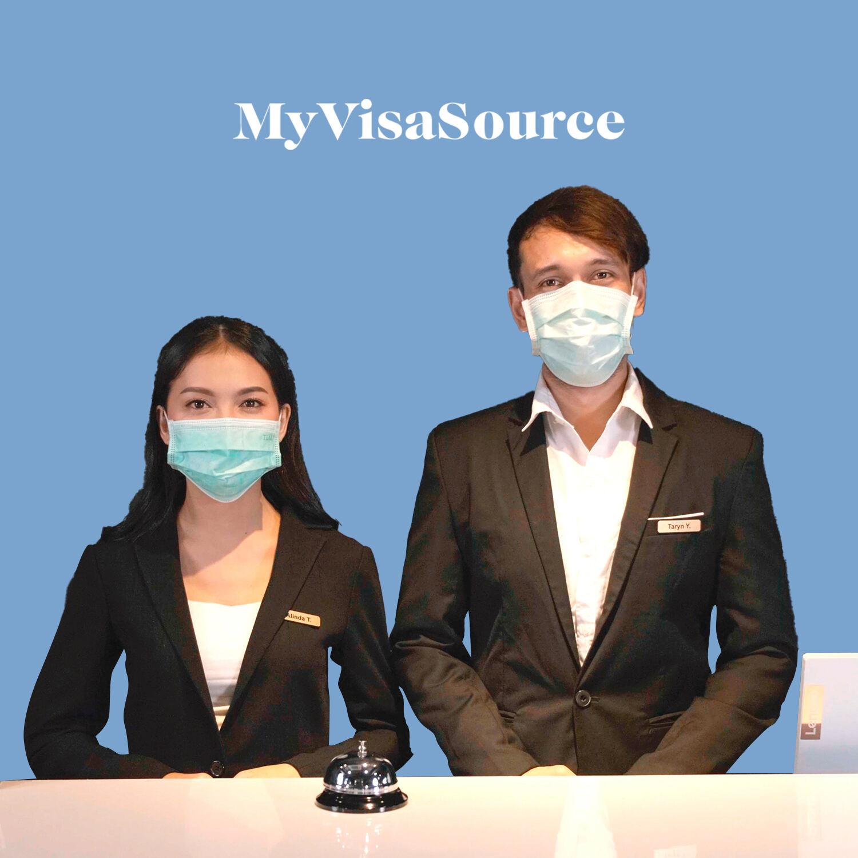 two hotel staff wearing covid masks my visa source