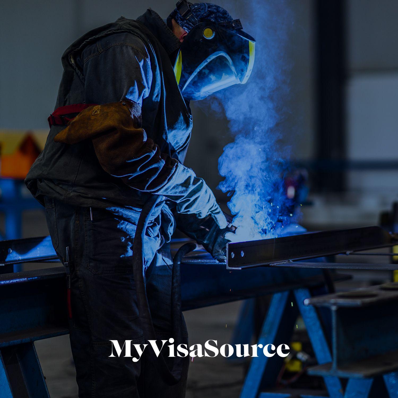 welder working on a metal beam my visa source