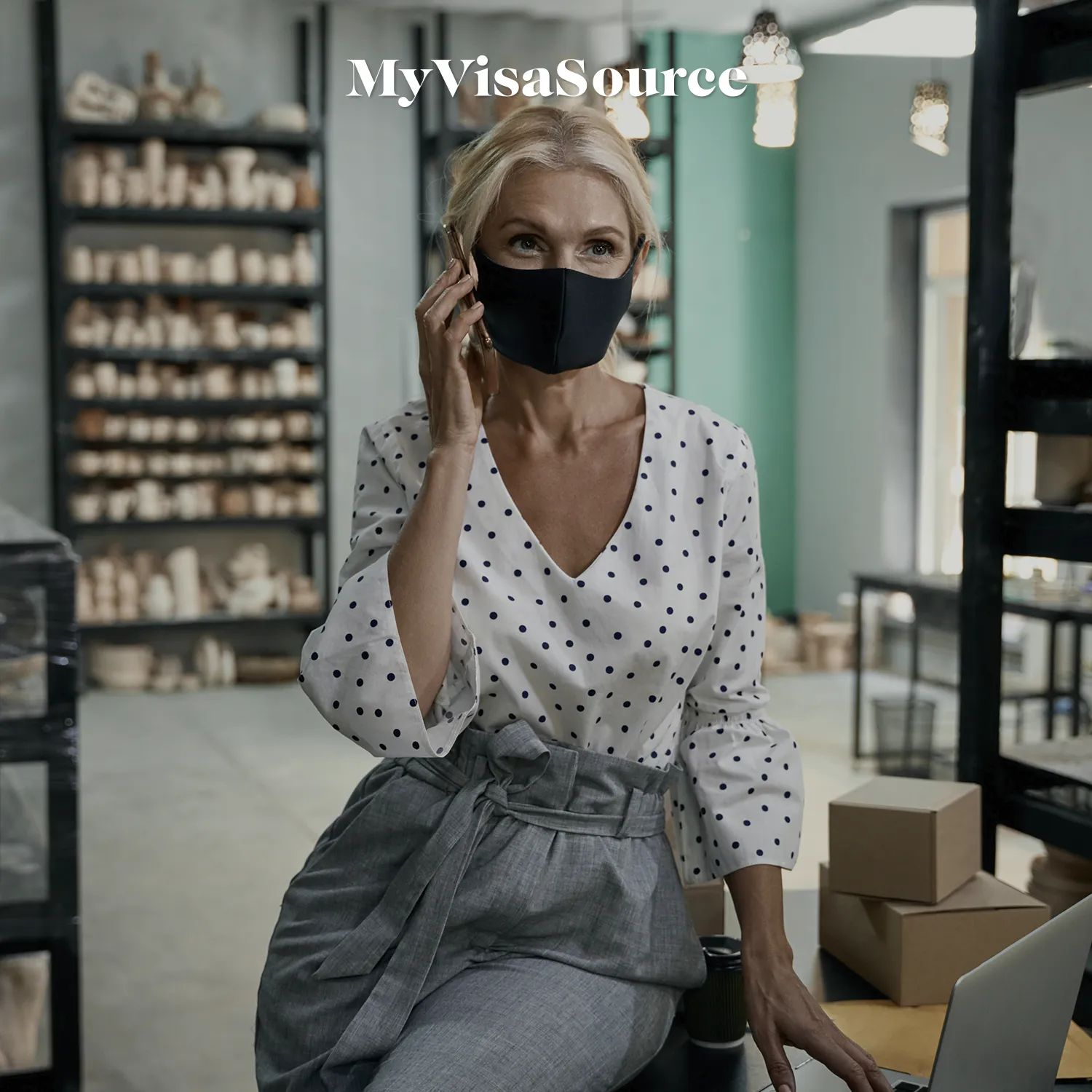 a-business-woman-talking-on-her-cell-with-a-facemask-by-my-visa-source