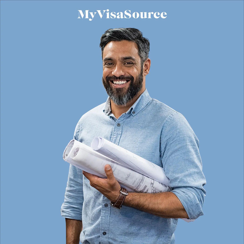 an-older-man-holding-blueprints-by-my-visa-source