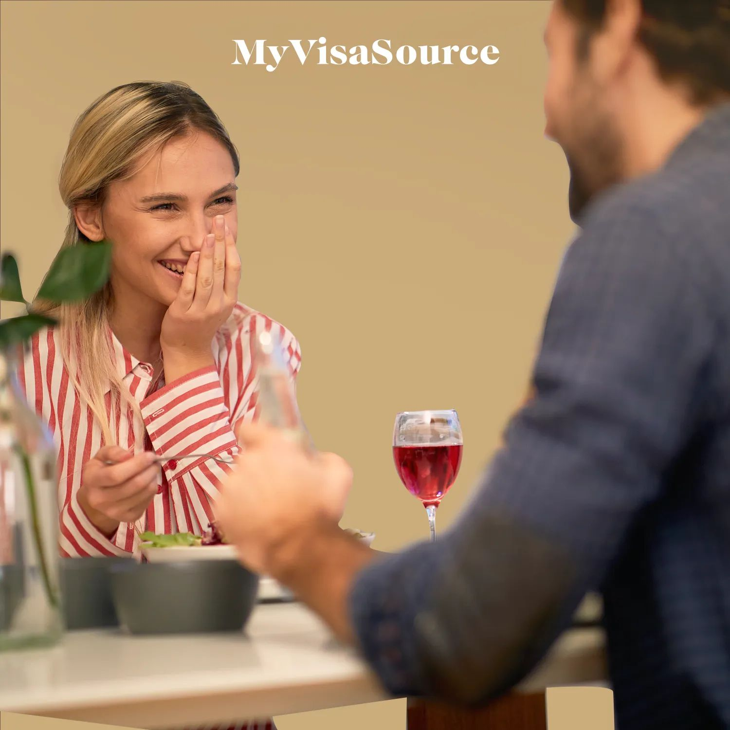 cheerful couple sharing a meal with brown background by my visa source