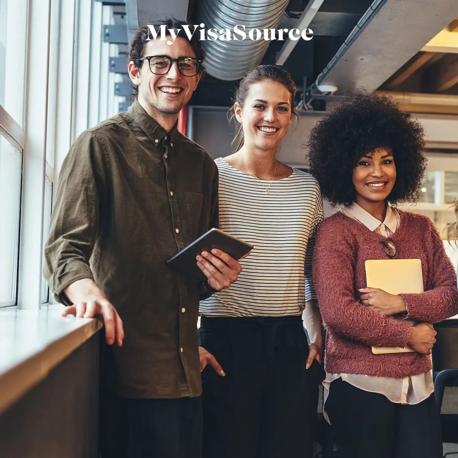 three cheerful co workers with tablets in hand at a casual workspace by my visa source