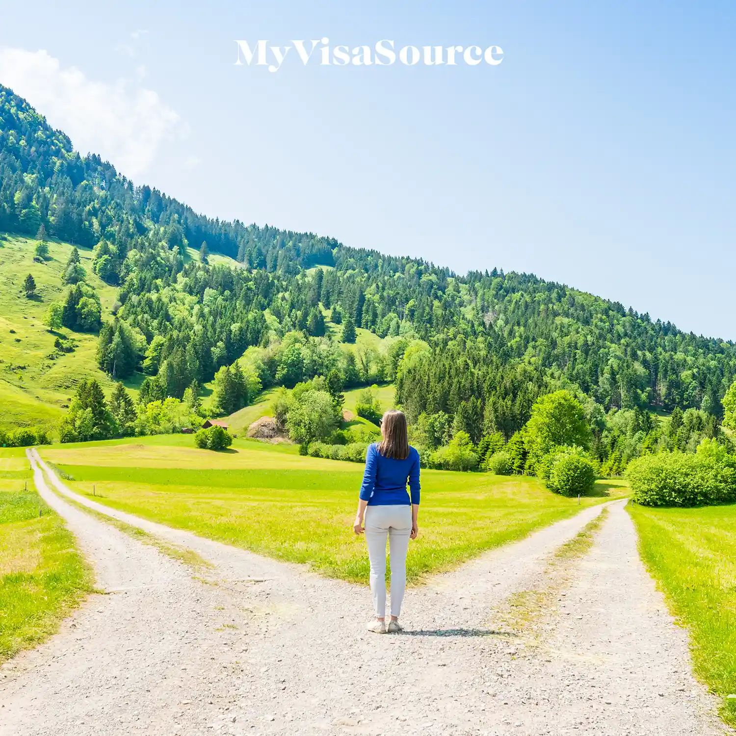 woman standing at a fork in the road with two different paths going into the hills and woods by my visa source